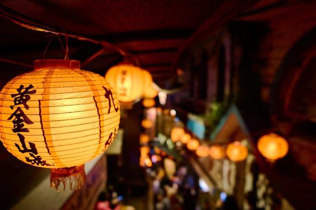 Primer plano de una linterna de papel chino con luces rodeadas por edificios Foto gratis