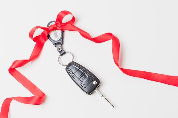 Primer plano de las llaves del auto con un lazo rojo como el presente en el fondo de pantalla blanco Foto Premium