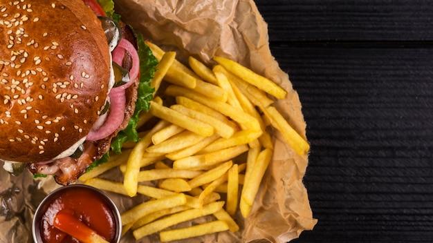 Primer plano para llevar hamburguesa con papas fritas y salsa de tomate Foto gratis