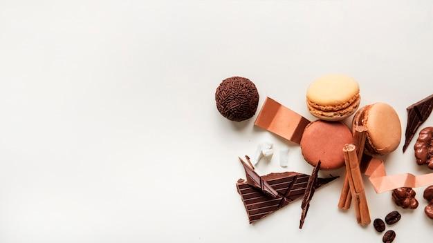 Primer plano de macarrones y bola de chocolate con ingredientes sobre fondo blanco Foto gratis