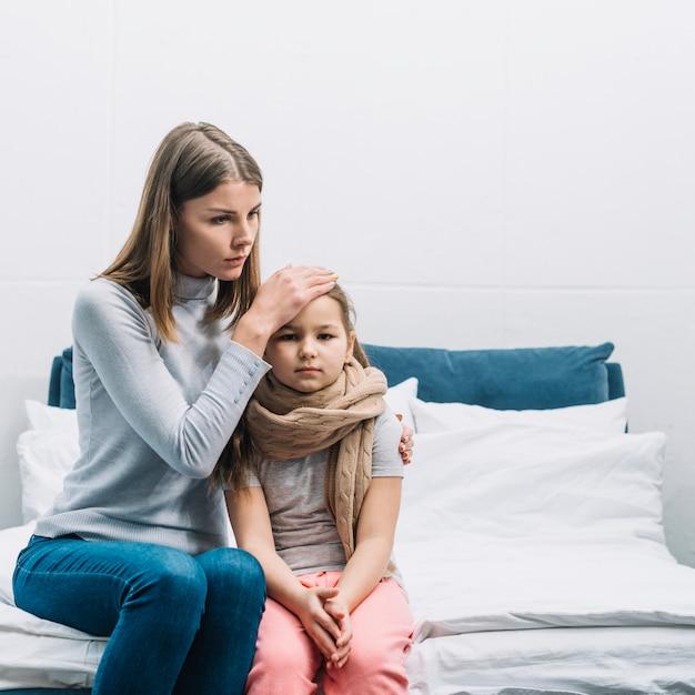 Primer plano de una madre tocando la frente de su hija con fiebre Foto gratis
