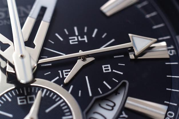 Primer plano de las manecillas, números y marcas de hora de un reloj negro Foto gratis