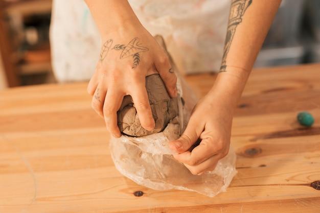 Primer plano de la mano del alfarero femenino que quita la arcilla de un papel de plástico sobre una mesa de madera Foto gratis