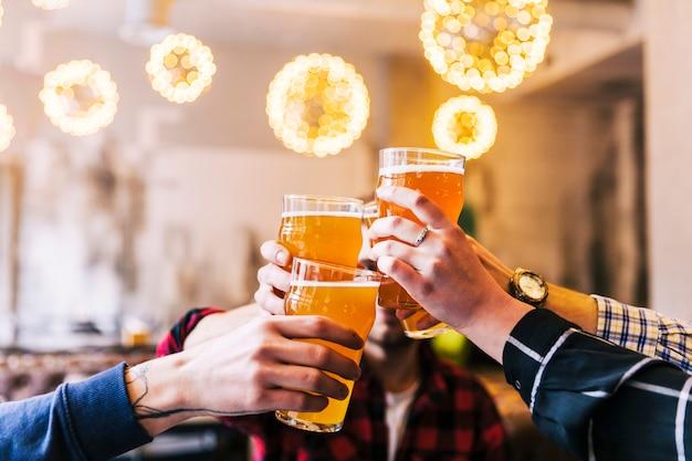 Primer plano de la mano de amigos tostado de los vasos de cerveza en la fiesta Foto gratis