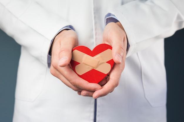 Primer plano de la mano del doctor sosteniendo corazón rojo con vendas cruzadas Foto gratis
