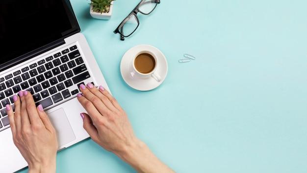 Primer plano de la mano de la empresaria escribiendo en la computadora portátil con una taza de café, lentes y Foto gratis