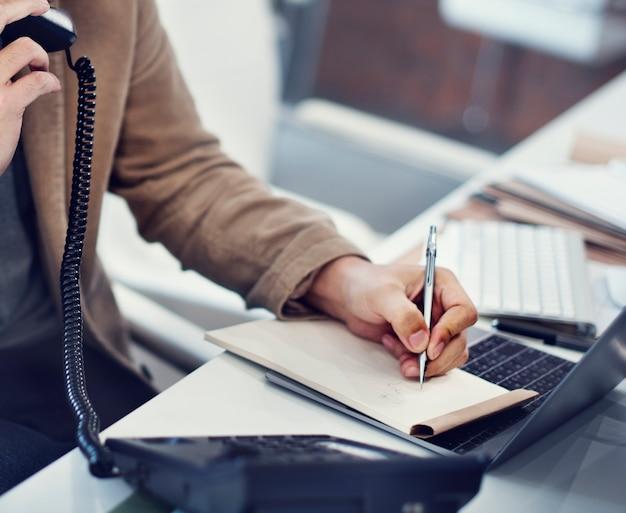 Primer plano de la mano escribiendo nota mientras está en el teléfono Foto gratis