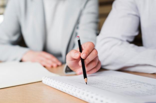 Primer plano de mano femenina con lápiz y marcado en el libro Foto gratis