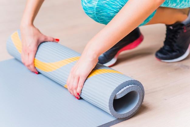 Primer plano de una mano femenina plegable estera de yoga Foto gratis