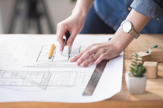 Primer plano de mano femenina trabajando en plano sobre escritorio de madera en el lugar de trabajo Foto Premium