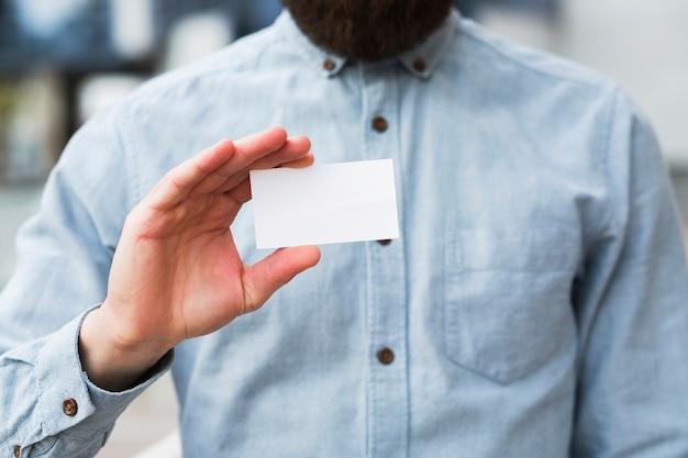 Primer plano de la mano de un hombre de negocios que muestra la tarjeta de visita en blanco blanco Foto gratis