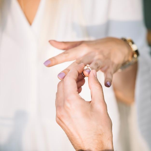 323bbea304aa Primer plano de la mano del hombre poniendo el anillo de compromiso en el  dedo de su novia