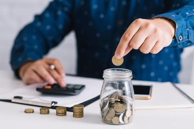 Primer plano de la mano del hombre poniendo la moneda en el vaso con calculadora Foto gratis