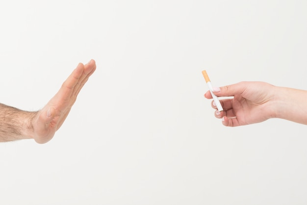 Primer plano de la mano de un hombre que dice no al cigarrillo dado por una persona aislada en el fondo blanco Foto gratis