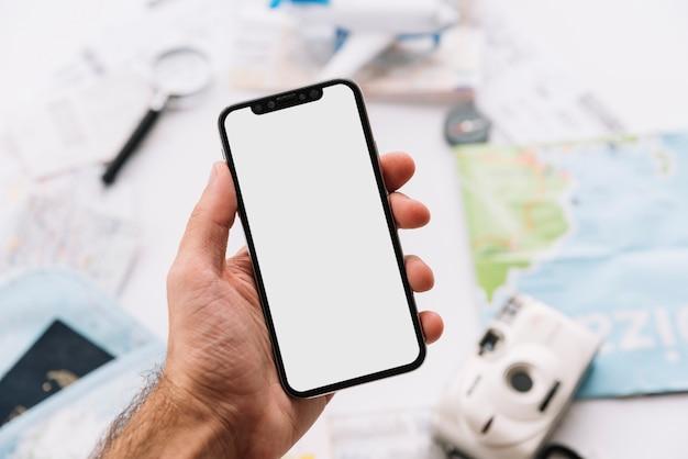 Primer plano de la mano del hombre que sostiene el móvil con pantalla blanca contra el fondo borroso Foto gratis
