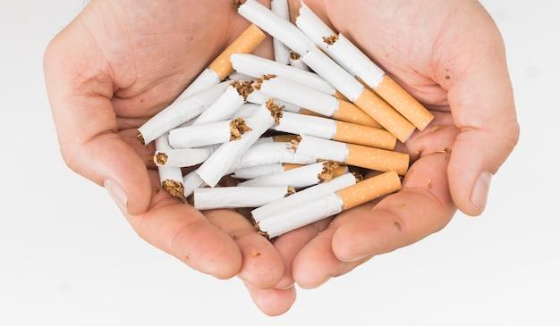 Primer plano de la mano del hombre sosteniendo cigarrillos rotos aislados sobre fondo blanco Foto gratis