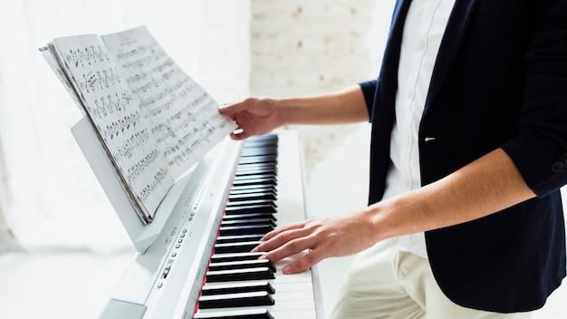 Primer plano de la mano del hombre tocando el piano Foto gratis