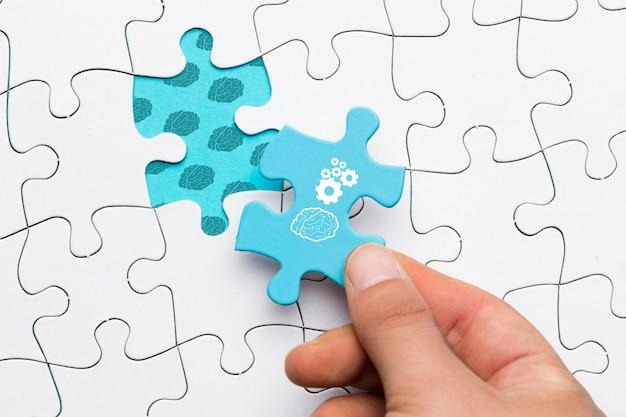 Primer plano de una mano humana con pieza de rompecabezas azul con dibujo de cerebro y rueda dentada Foto gratis