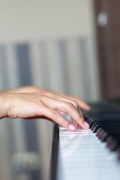 Primer plano de la mano de un intérprete de música clásica tocando el piano o sintetizador electrónico (teclado de piano) lección de niña en piano Foto Premium