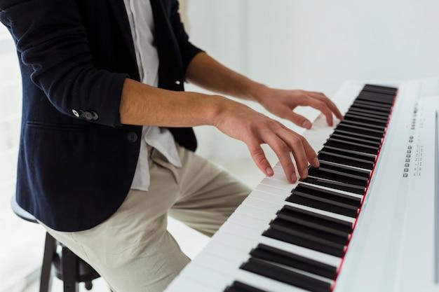 Primer plano de la mano del joven tocando el piano Foto gratis