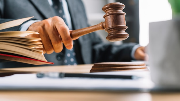 Primer plano de la mano del juez masculino golpeando el martillo en la mesa Foto Premium