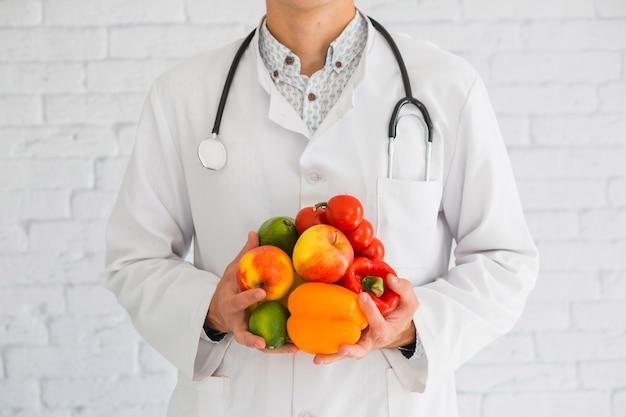 Primer plano de la mano del médico de sexo masculino con productos frescos frutas y verduras saludables Foto gratis