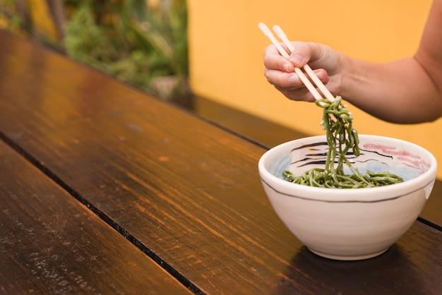 Primer plano de la mano de una mujer comiendo algas chuka sésamo con palillos Foto gratis