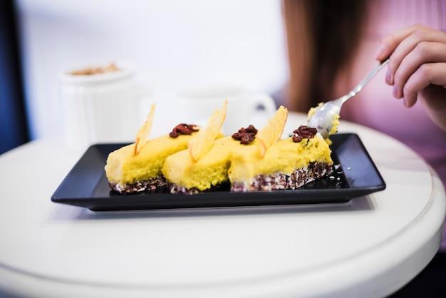 Primer plano de la mano de una mujer comiendo rebanada de pastel con una cuchara en una bandeja negra sobre la mesa blanca Foto gratis