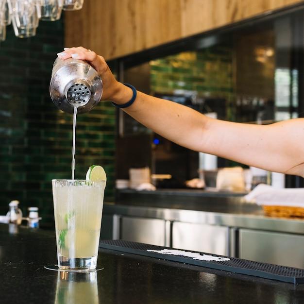 Primer plano de la mano de una mujer haciendo cóctel en barra de bar Foto gratis