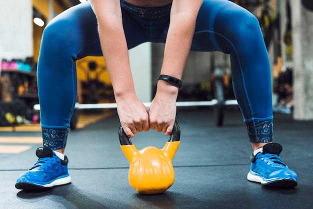Primer plano de la mano de una mujer haciendo ejercicio con bola de caldera Foto gratis
