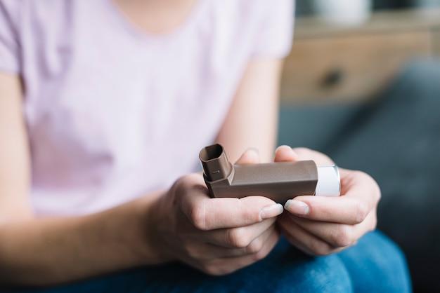 Primer plano de la mano de una mujer con inhalador de asma Foto gratis