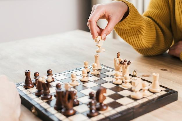 Primer plano de la mano de la mujer jugando al tablero de ajedrez en el escritorio de madera Foto gratis