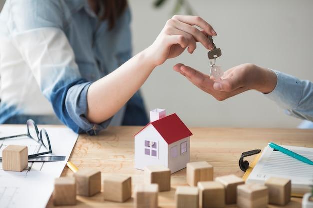 Primer plano de la mano de la mujer que da la llave de la casa al hombre sobre mesa de madera Foto gratis