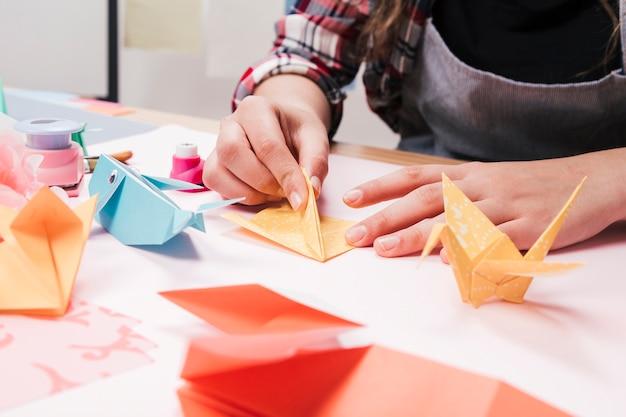 Primer plano de la mano de la mujer que hace arte creativo del arte usando el papel del origami Foto gratis