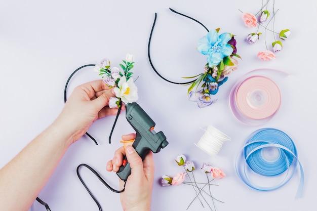 Primer plano de la mano de la mujer que pega las flores en la cinta para el cabello con una pistola eléctrica de pegamento caliente sobre fondo blanco Foto gratis