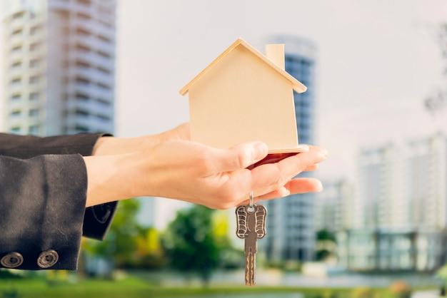 Primer plano de la mano de la mujer que sostiene el modelo de la casa de madera y las llaves contra el telón de fondo borroso Foto gratis