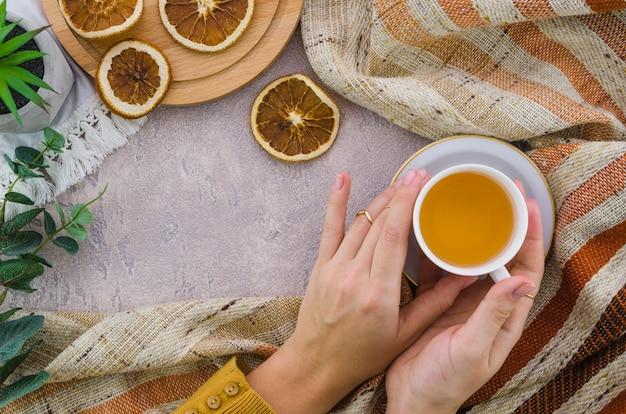 Primer plano de la mano de una mujer sosteniendo la taza de té de hierbas y té de limón seco Foto gratis