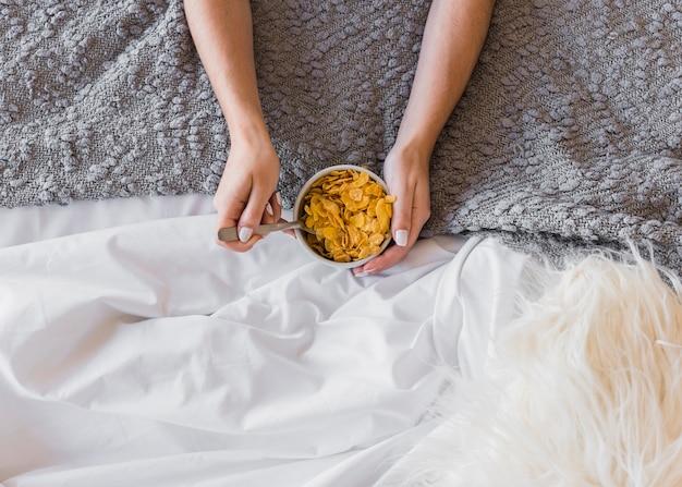 Primer plano de la mano de una mujer sosteniendo un tazón de copos de maíz sobre la alfombra y la manta blanca Foto gratis