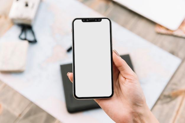 Primer plano de la mano de una mujer sosteniendo un teléfono inteligente con pantalla en blanco Foto Premium