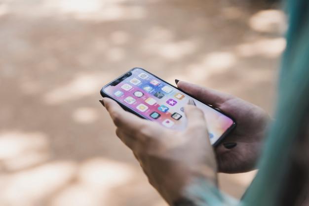Primer plano de la mano de una mujer sosteniendo un teléfono móvil con varios íconos de aplicaciones en la pantalla Foto gratis