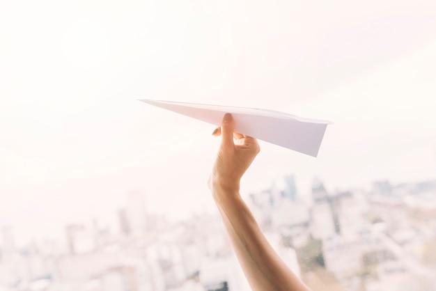 Primer plano de la mano de una mujer volando un avión de papel hecho a mano contra el paisaje urbano Foto gratis