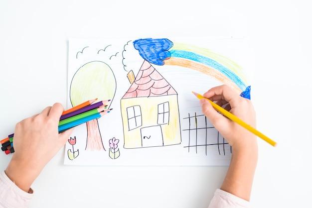Primer plano de la mano de la niña dibujando la casa con lápiz de color sobre papel con fondo blanco Foto gratis