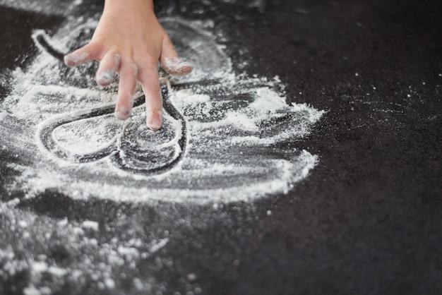 Primer plano de la mano de una niña dibujando heartshape en harina Foto gratis
