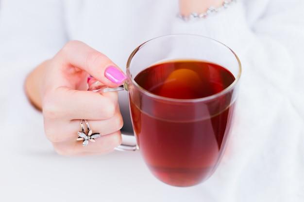 Primer plano de la mano de la niña con un hermoso anillo y manicura que sostiene una taza de té transparente Foto Premium