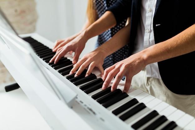 Primer plano de la mano de la pareja tocando el teclado del piano Foto gratis