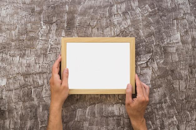 Primer plano de la mano de una persona colocando un marco blanco en la pared Foto gratis
