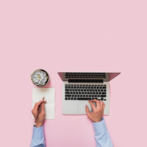 Primer plano de la mano de una persona de negocios escribiendo en la computadora portátil y escribiendo en papel con lápiz sobre fondo rosa Foto gratis