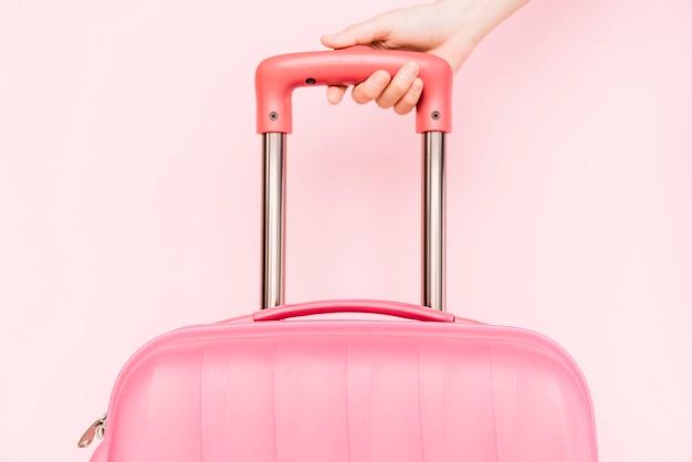 Primer plano de la mano de una persona que sostiene el asa del equipaje de viaje contra un fondo rosa Foto gratis