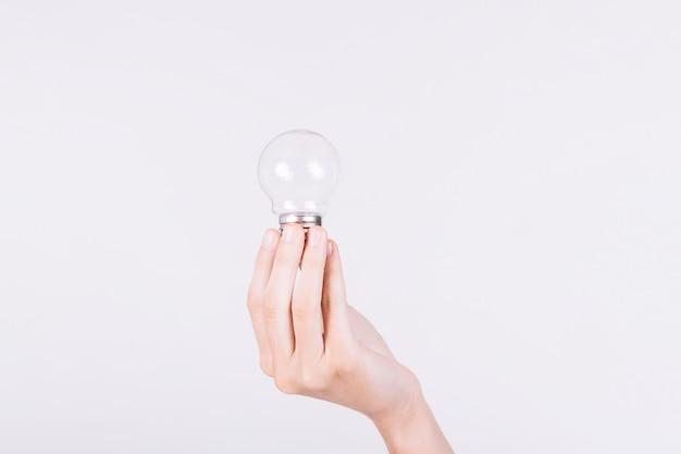 Primer plano de la mano de una persona que sostiene la bombilla sobre fondo blanco Foto gratis