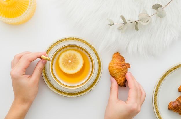Primer plano de la mano de una persona que tiene croissant con té de limón sobre fondo blanco Foto gratis